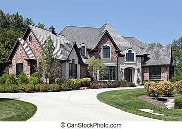 Large brick home in suburbs with circular driveway