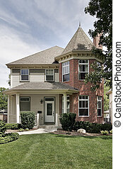 Large brick home with turret and lawn