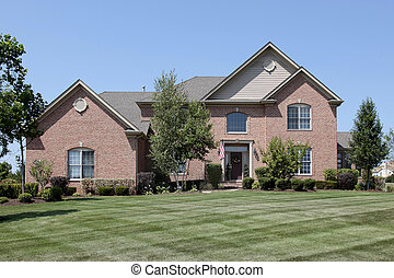 Large brick home with window above entry
