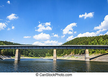 Large bridge over a lake near a forest