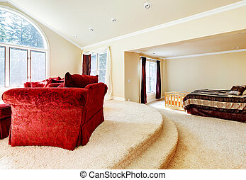 Large bright bedroom with red sofa and beige tones.