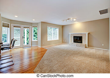 Large bright empty new living room with fireplace and beige carpet.