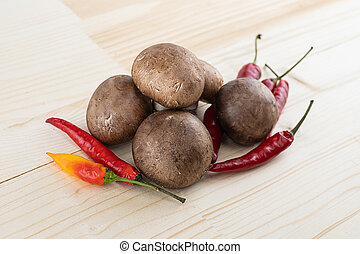 large brown champignons whole mushrooms lie on the pods of red chili on a wooden background