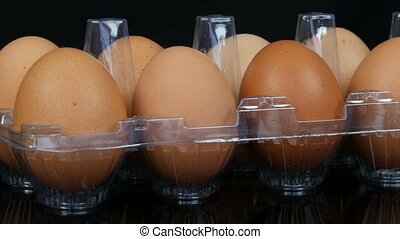 Large brown chicken eggs in a transparent plastic tray on...