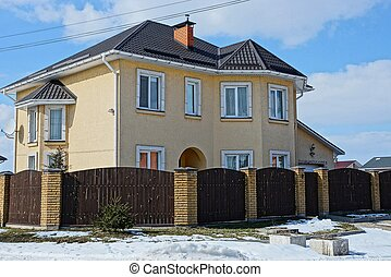large brown house after a wooden fence in the street in the snow