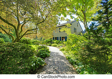 Large brown house exterior with green summer garden.