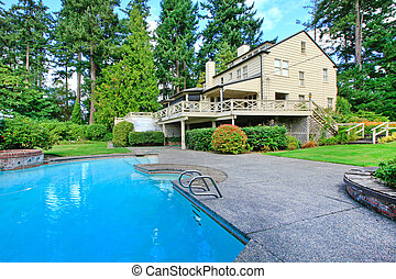 Large brown house exterior with summer garden and swimming pool. Northwest.