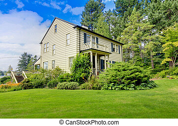 Large brown house exterior with summer garden. Northwest.