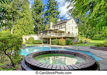Large brown house exterior with summer garden with pool.