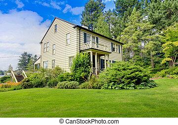 Large brown house exterior with summer garden. Northwest.