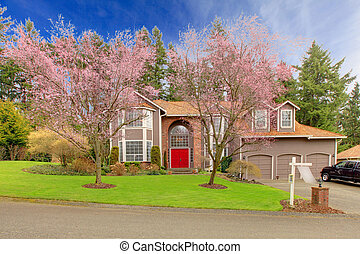 Large brown house with red door in a spring time