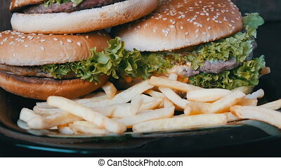 Large burgers with cutlets and lettuce leaves close view. French fries are topped on burgers