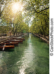 Large canal with boats and trees in the city center of Annecy.