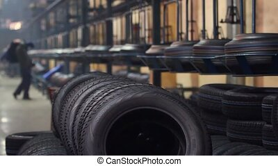 Large car tire factory. - Stacks of new tires in shop near...