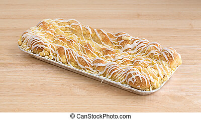 Large cheese danish in tinfoil tray on a wood table
