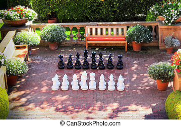 life-sized chess pieces set up on a patio with benches and flowers in background