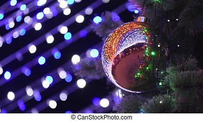 Large Christmas ball hanging on the Christmas tree in the background blurry lights garland