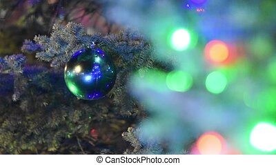 Large Christmas ball hanging on the Christmas tree in the foreground blurry lights garland