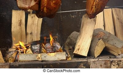 Large chunks of delicious pork hams cooked on an open fire. The street food. Food outdoors. Camping and cooking on a spit over the fire, man cooks large pieces of meat on a spit on fire, closeup
