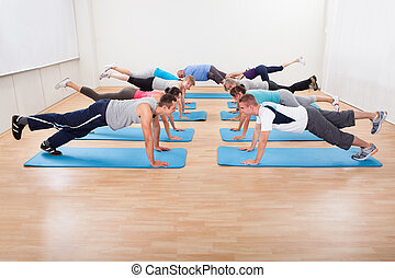 Large class of people working out in a gym