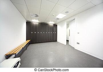 large clean locker room, gray floor and ceiling, black...
