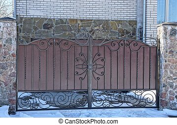 brown metal gate on a fence in the street in the snow