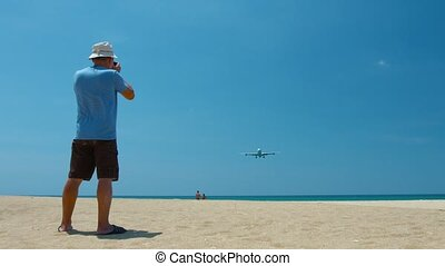 Video 3840x2160 - Photographer shooting a large, commercial airliner as it cruises low over a beach on final landing approach to Phuket International Airport in Thailand.
