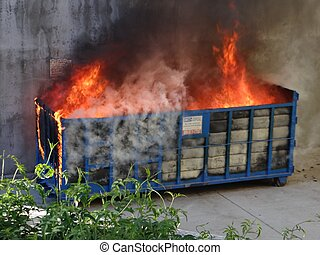 Large commercial dumpster burning on fire in an alleyway