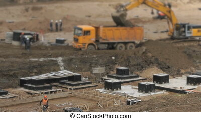 Large construction area in summer - Yellow excavator loads...