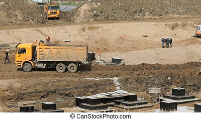 Large construction area in summer - Yellow truck drives on...