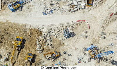 Large construction site including several excavators and...