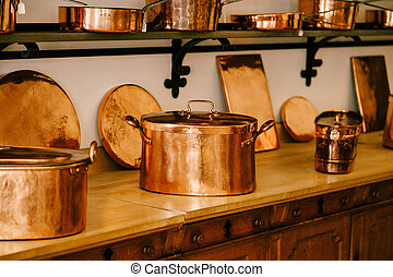 Large copper pots with hot coasters on the countertop with copper saucepans and saucepans on shelves to be attached to the white wall. High quality photo