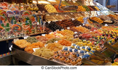 Large Counter with Colorful Sweets in La Boqueria Market. Barcelona, Spain.