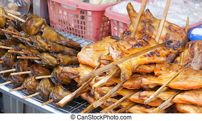 Large counter with various Fried fish and chicken on wooden sticks. Counter with variety of Thai food. Asian street food