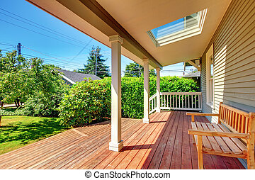 Large covered porch with skylight and wood bench and floor...