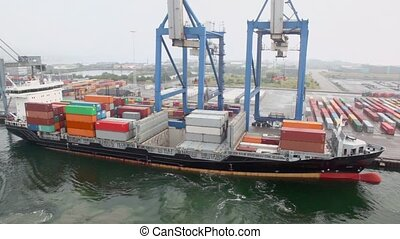 Large cranes and vessel with containers on board in seaport at day