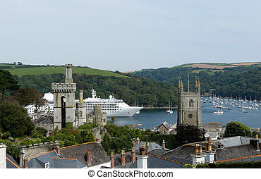 Large cruise ship and small sailboats from an aerial perspective above Fowey estuary. Cornwall, UK