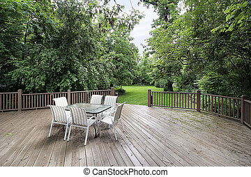 Large wooden deck with table and chairs leading to backyard