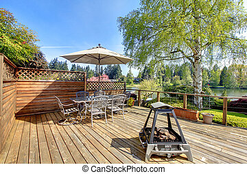 Large deck with furniture and umbrella with lake view.