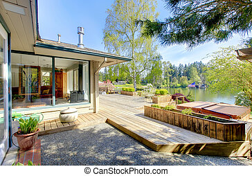 Large deck with the house and a lake view.