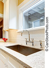 Large deep metal kitchen sink with granite countertops. -...