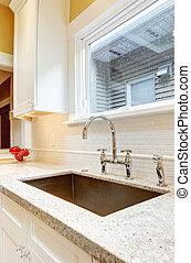 Large deep metal kitchen sink with granite countertops.