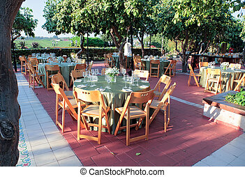 Large dining table set for wedding located in green garden among the trees.