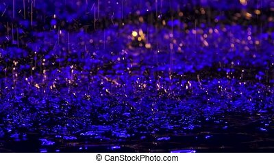 Large drops of rain create small splashes on the surface of the water illuminated by a blue soffit. Photographed on a black background. Close up. Slow motion