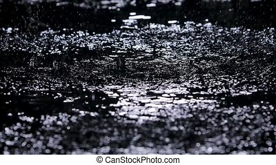 Large drops of rain drip onto the shiny surface of the water. Shot in a dark studio with white neon lighting effects. Slow motion. Close up.