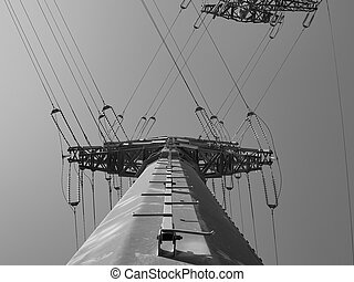 Large electric pole with wires against the blue sky black and white photo