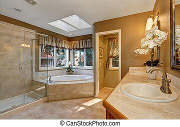 Large elegant master bathroom with tile floors, and glass shower.