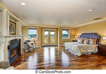 Large elegant master bedroom with fireplace.