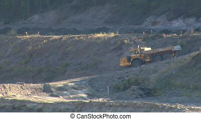 large empty dump truck drives over dirt road