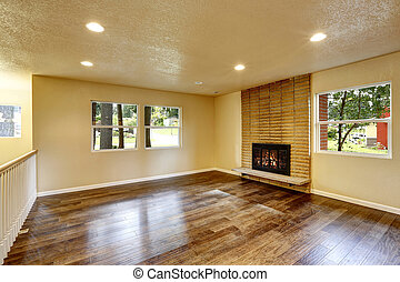 Large empty living room with fireplace